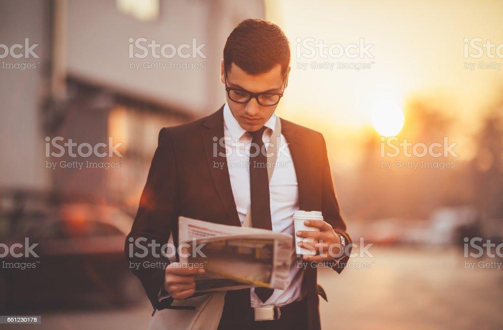 Businessman reading newspaper stock photo