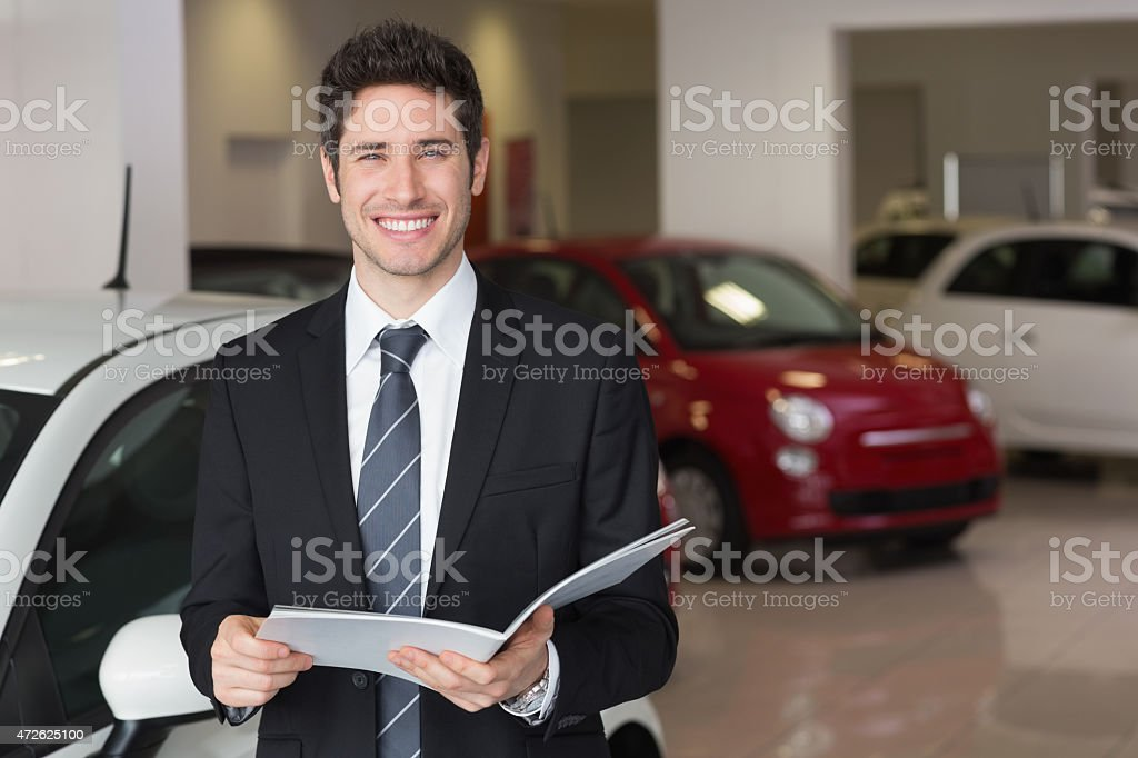 Businessman reading over a booklet smiling at camera stock photo