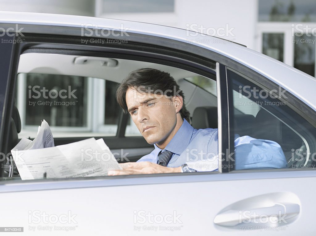 Businessman reading paper in backseat of car royalty-free stock photo