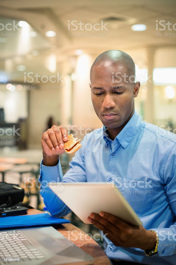 Businessman reading tablet during lunch in food court stock photo