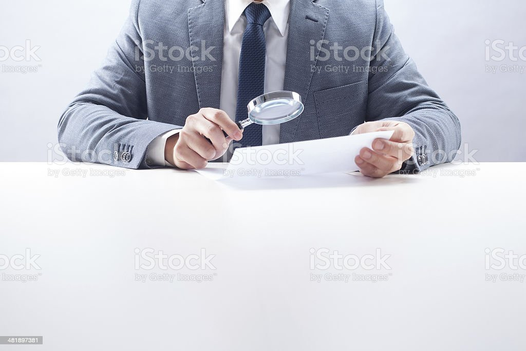 Businessman Reading with Magnifying Glass stock photo