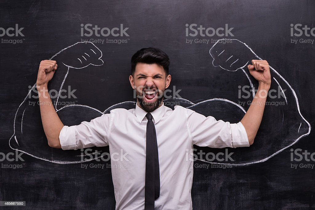 Businessman ready to win with painted muscular arms on chalkboard stock photo