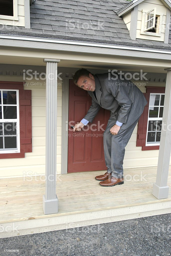 Businessman Real Estate Agent at Front Door of Small House stock photo