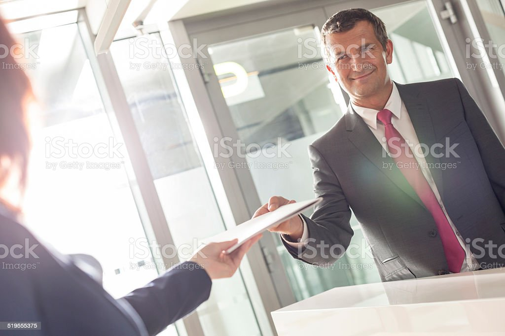 Businessman receiving document from receptionist in office stock photo