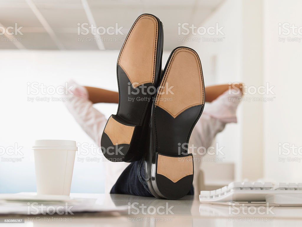 Businessman Reclining With His Feet Up On Desk stock photo