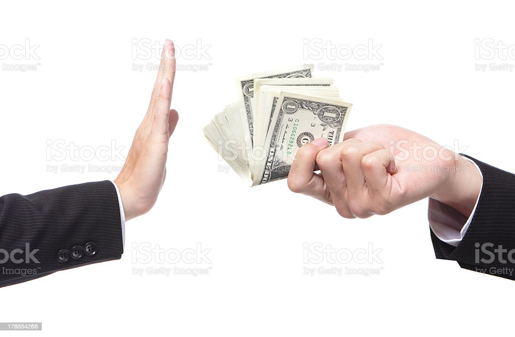 A businessman refusing an offering of money from another man stock photo
