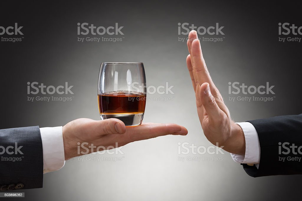 Businessman Rejecting Whisky Offered By Businessperson stock photo