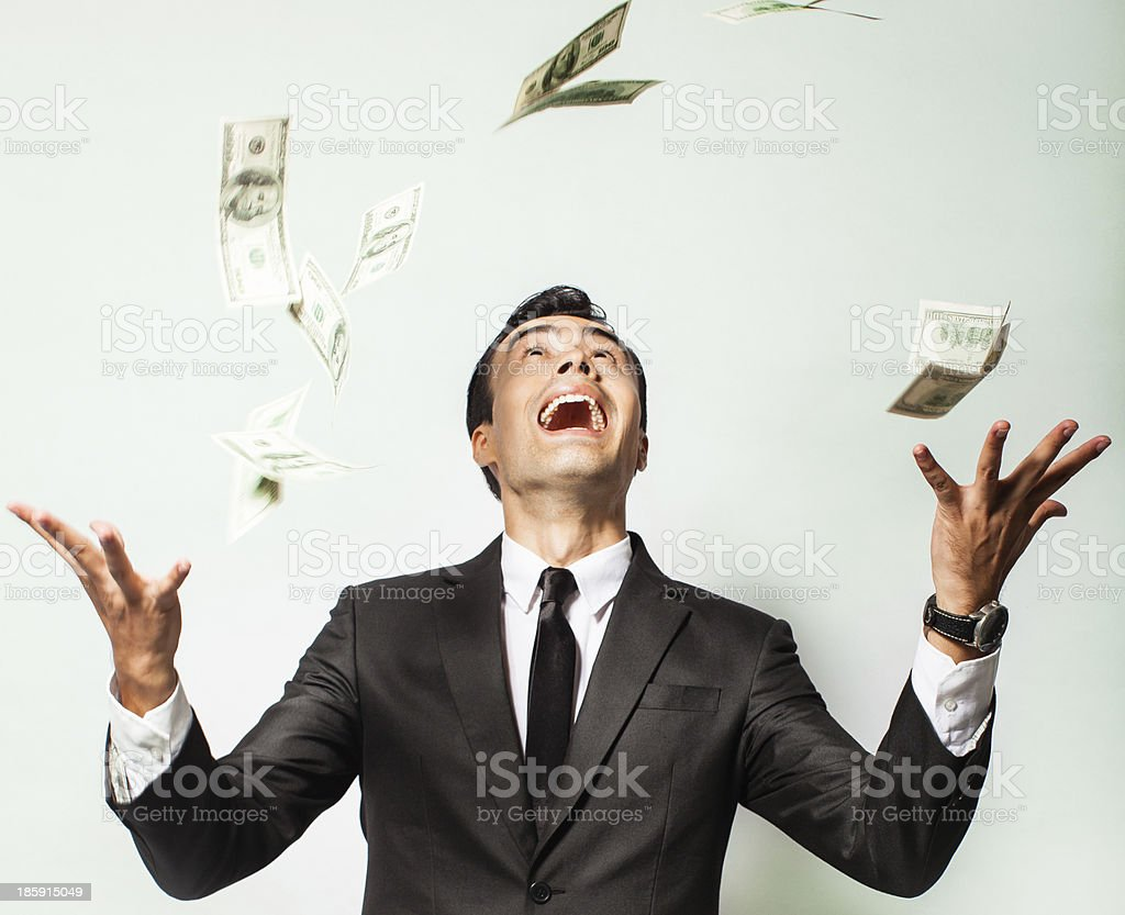 Businessman rejoicing for his success with hundred dollar bills. stock photo