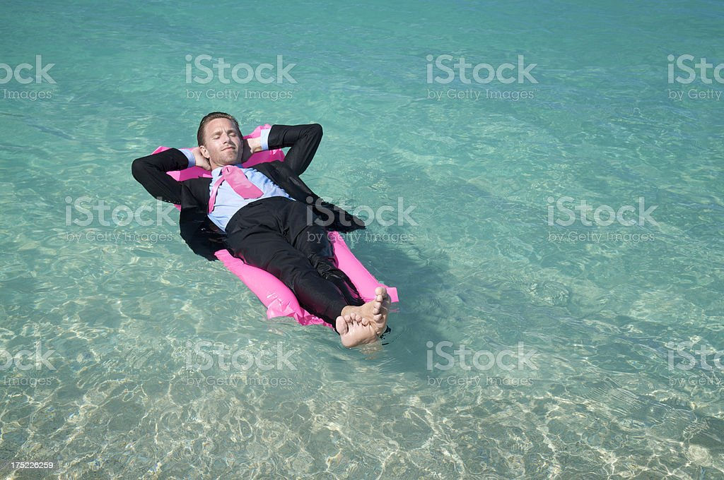 Businessman Relaxes Floating on Lilo in Tropical Water stock photo