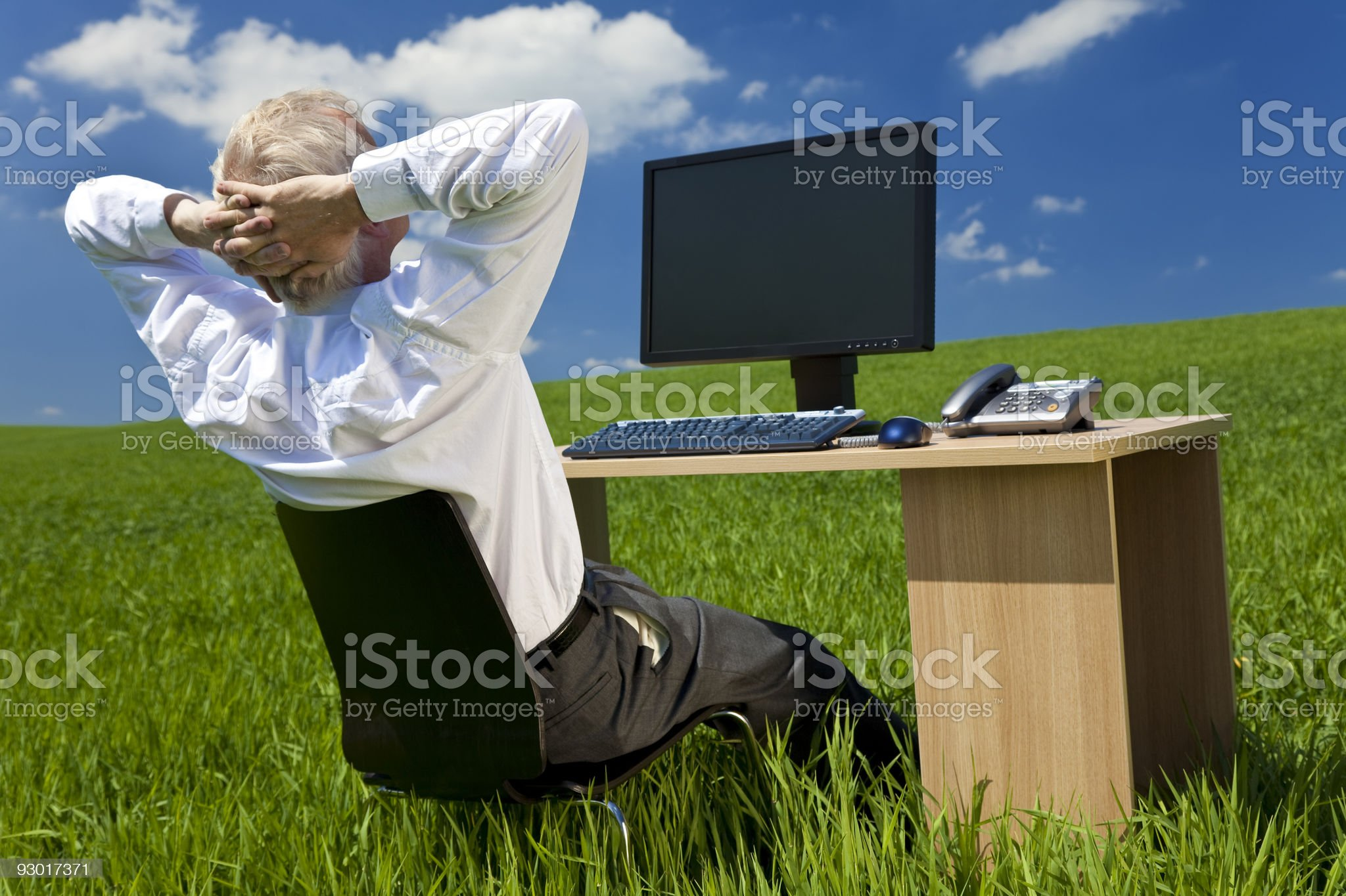 Businessman Relaxing at Desk With Computer In A Green Field royalty-free stock photo