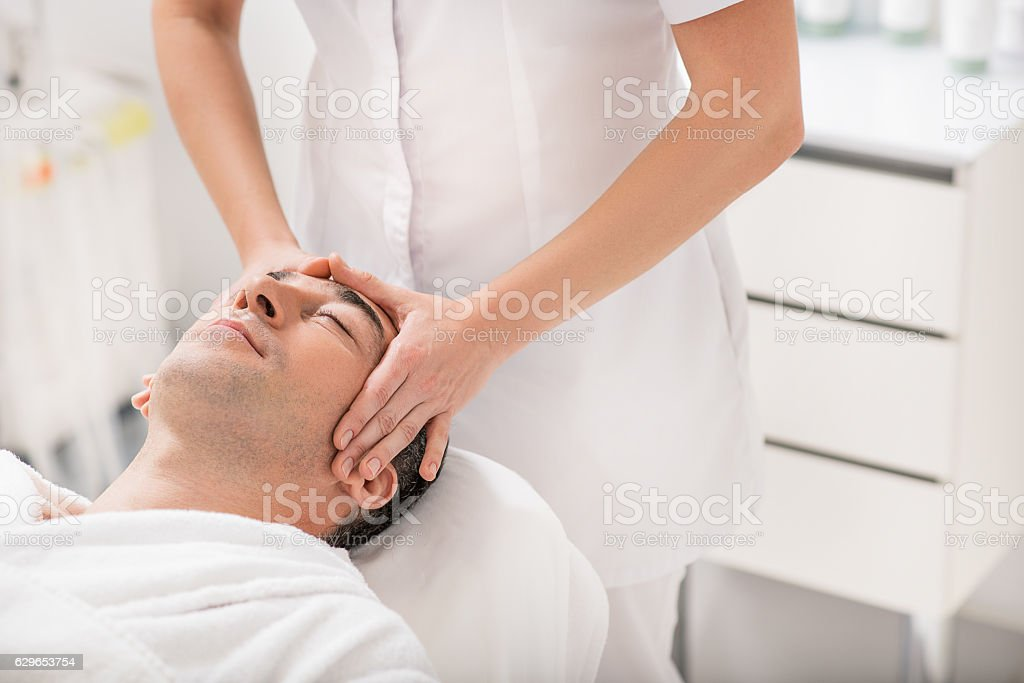 Businessman relaxing during massage at spa stock photo