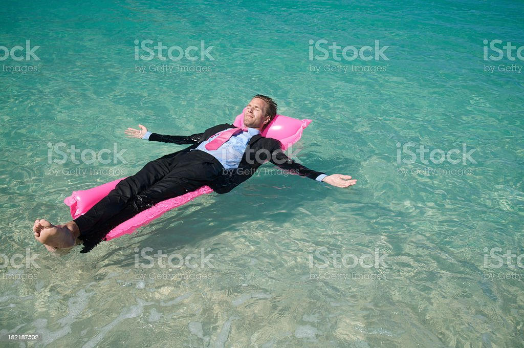 Businessman Relaxing Floating on Pink Pool Raft stock photo