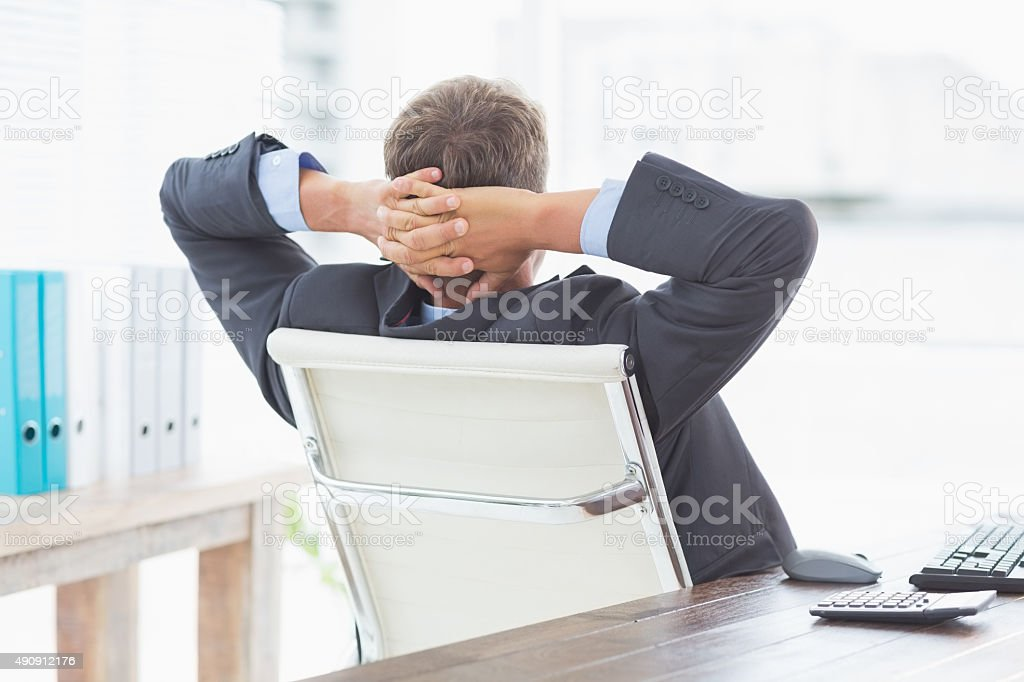 Businessman relaxing in a swivel chair leaning back stock photo