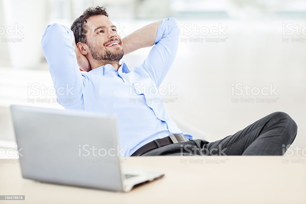 Businessman relaxing  in armchair stock photo