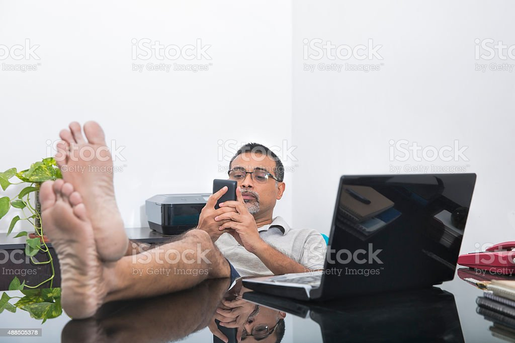 Businessman relaxing in his home office wearing casual dress stock photo