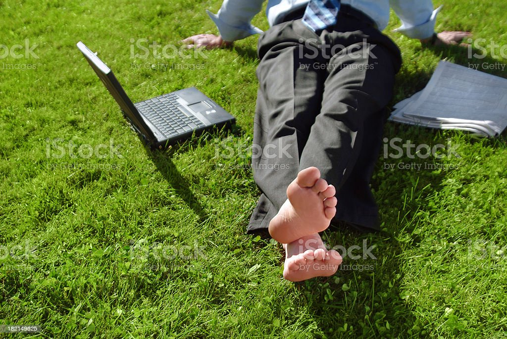 Businessman Relaxing in the Grass with his Shoes Off royalty-free stock photo