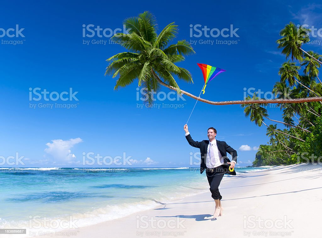 Businessman relaxing on a tropical palm fringed beach royalty-free stock photo