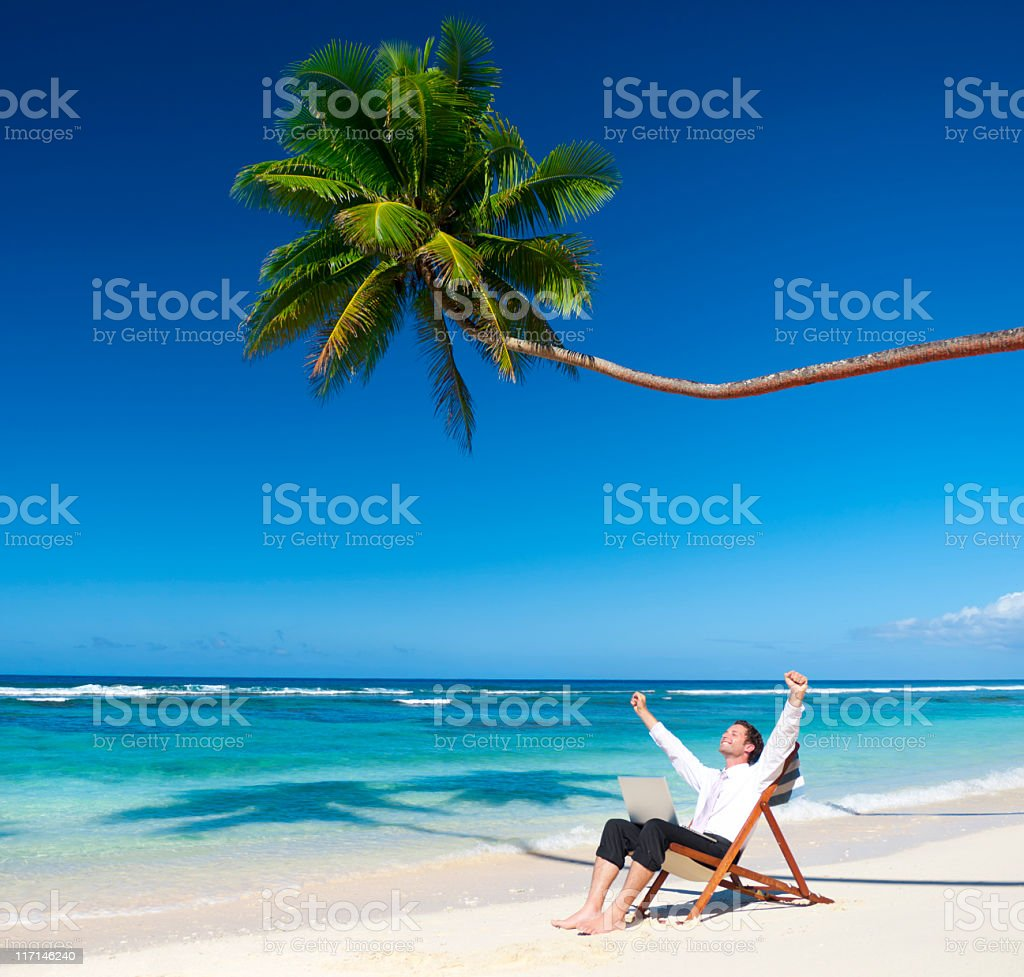 Businessman relaxing on an idylic palm fringed beach royalty-free stock photo