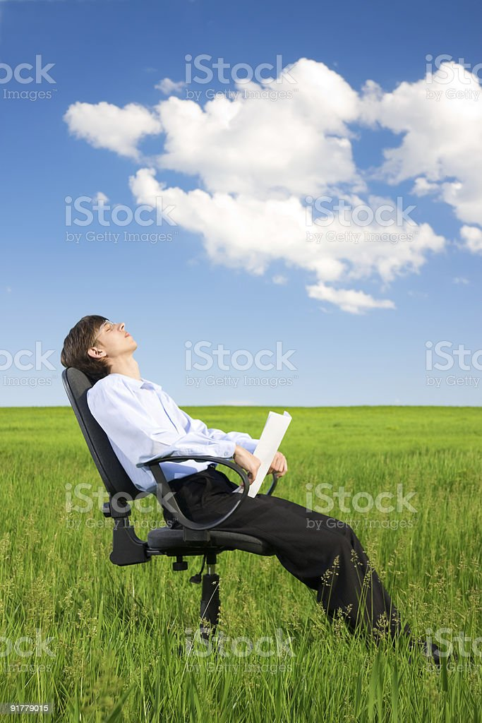 Businessman relaxing on grassland under blue sky royalty-free stock photo