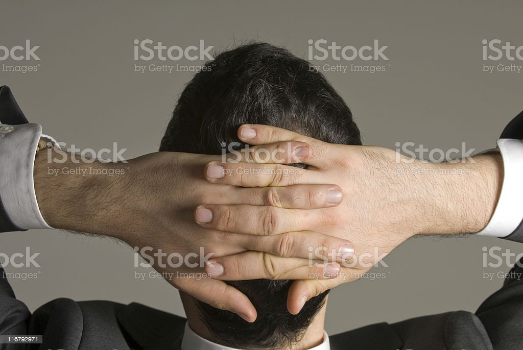Businessman relaxing with hands behind head royalty-free stock photo