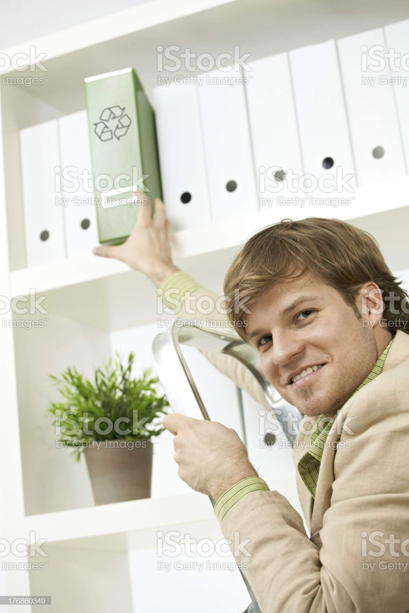 Businessman removing green folder from shelf royalty-free stock photo
