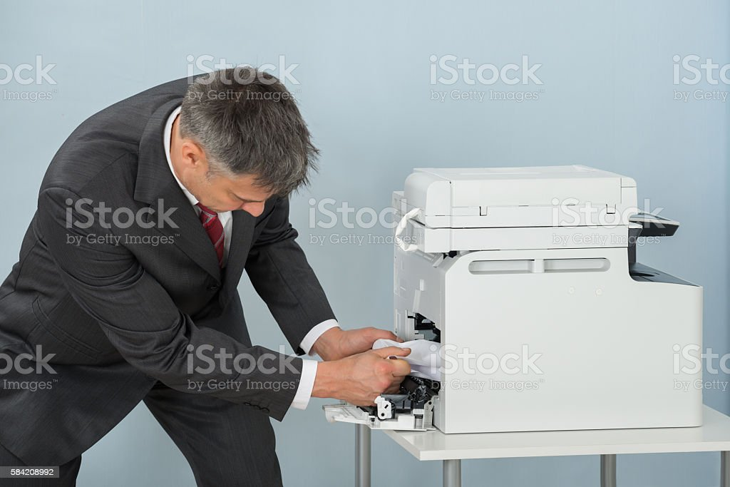 Businessman Removing Paper Stuck In Printer At Office stock photo