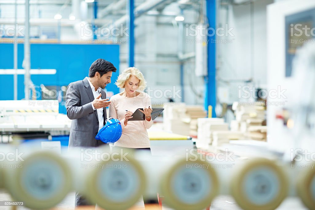 Businessman reporting production details to senior manager stock photo