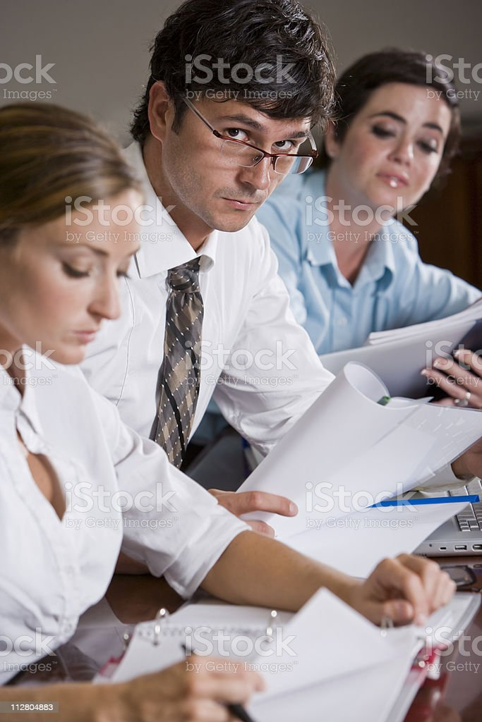 Businessman reviewing documents with female colleagues royalty-free stock photo