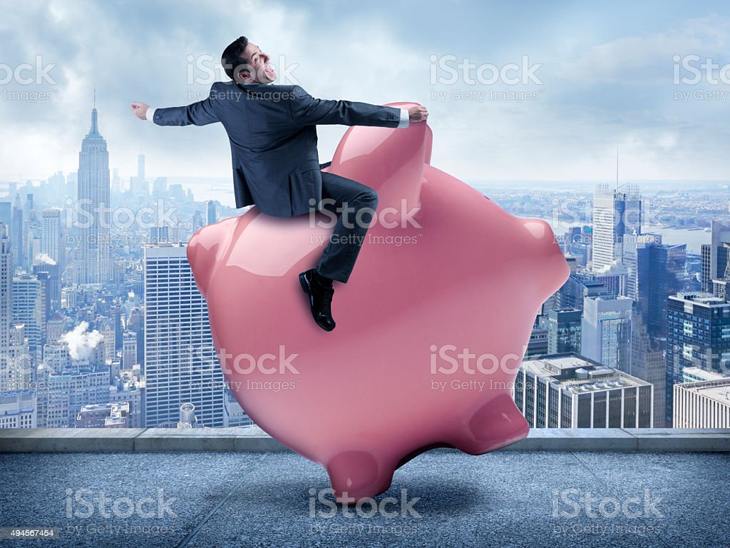 Businessman Riding A Piggy Bank In Urban Scene stock photo