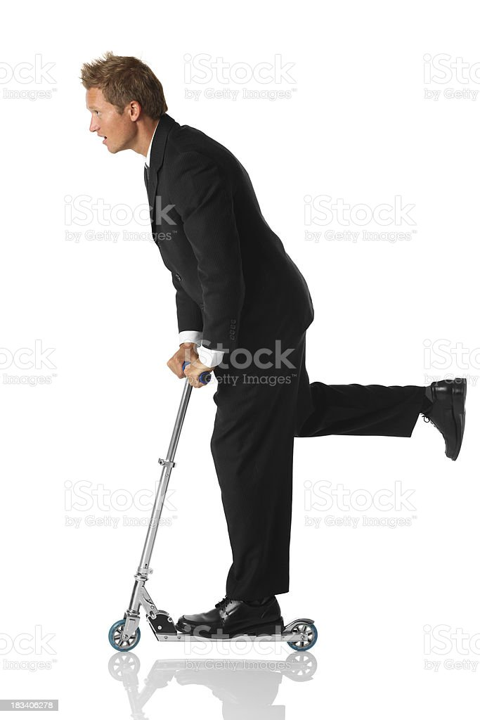 Businessman riding a push scooter royalty-free stock photo