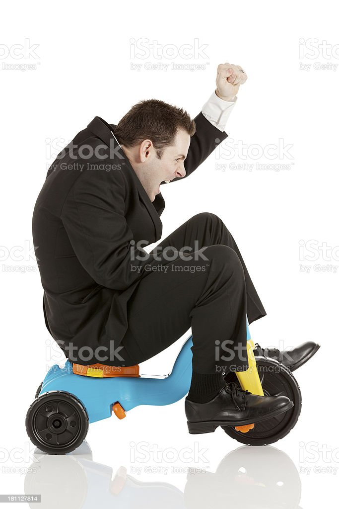 Businessman riding a tricycle against white royalty-free stock photo