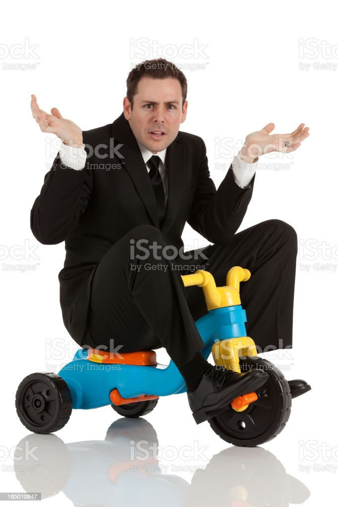 Businessman riding a tricycle royalty-free stock photo