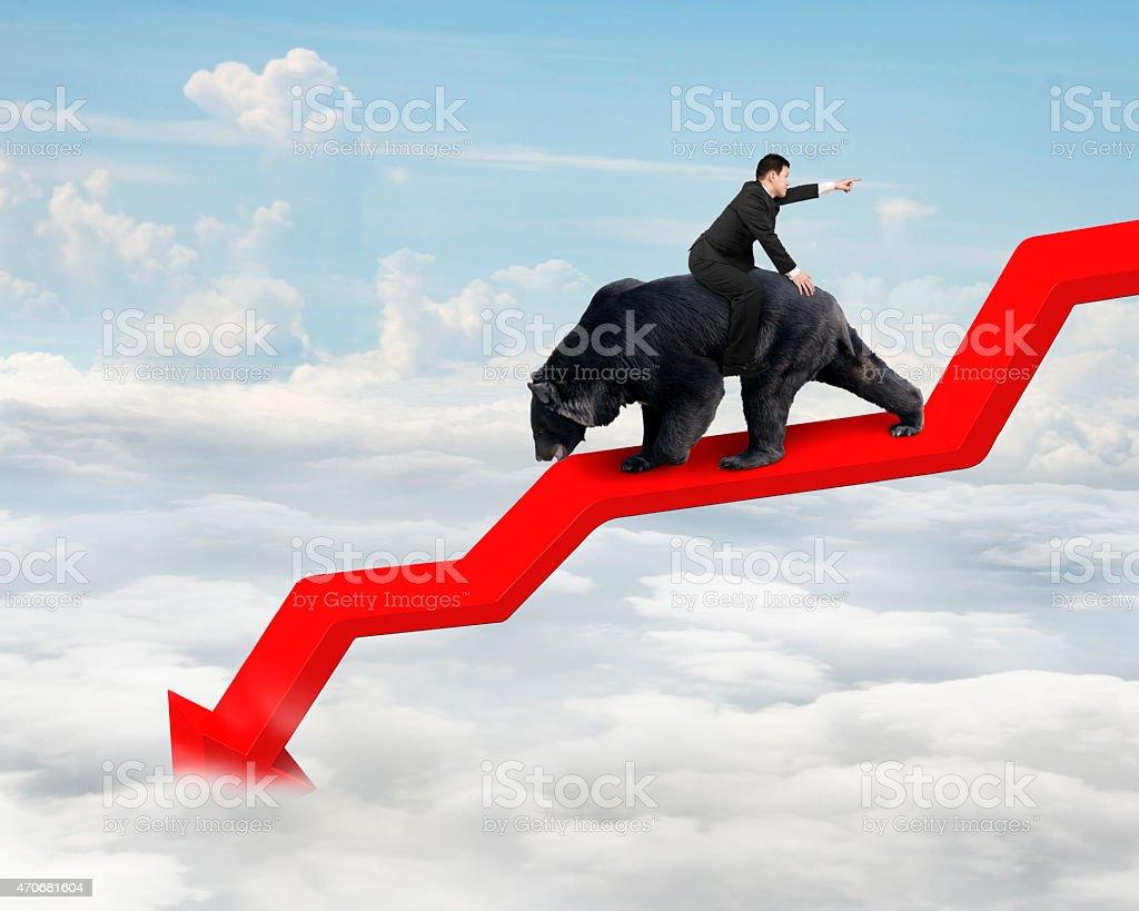 Businessman riding bear on arrow downward trend line with sky stock photo