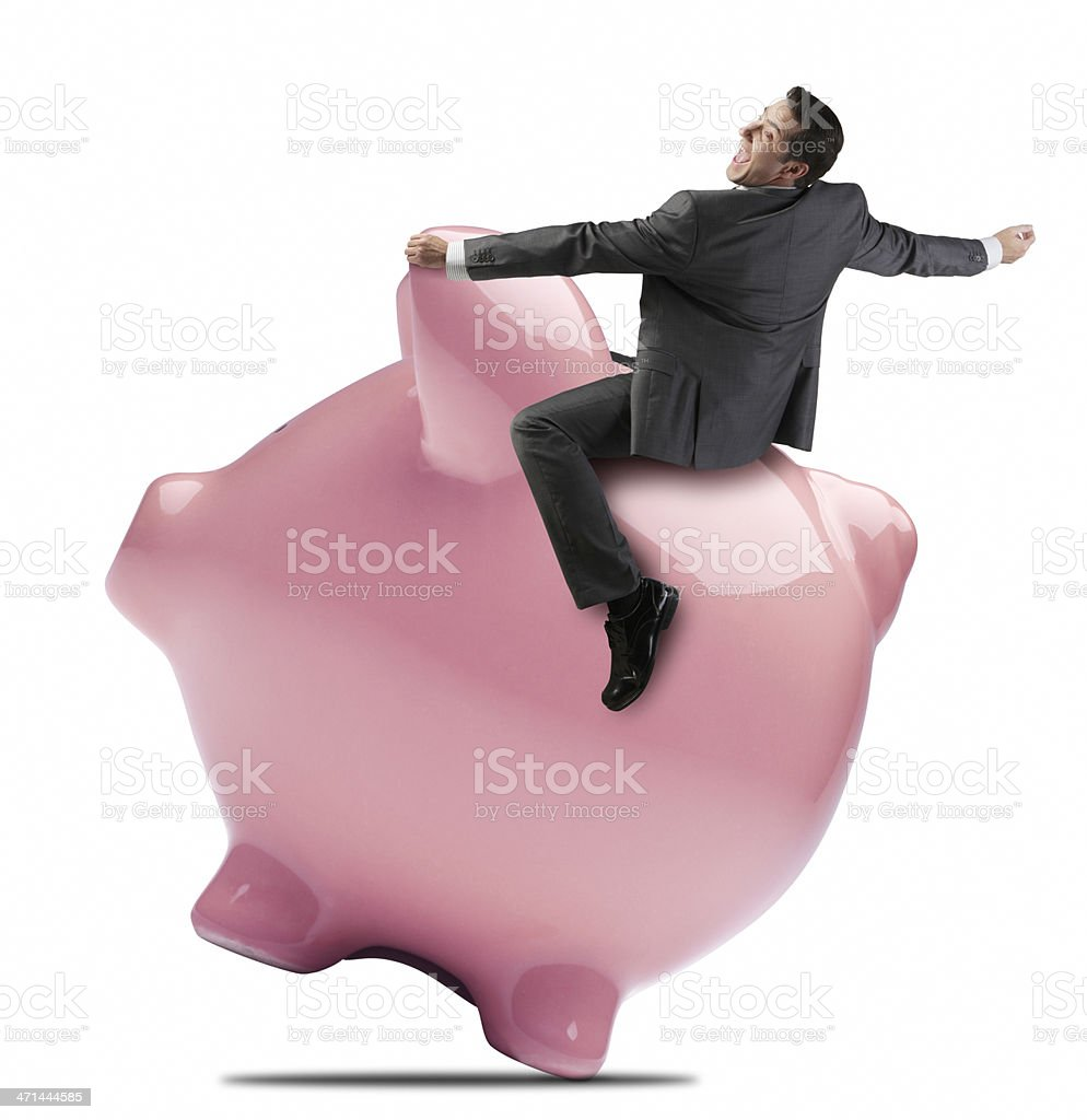 Businessman riding on back of pink piggy bank. royalty-free stock photo