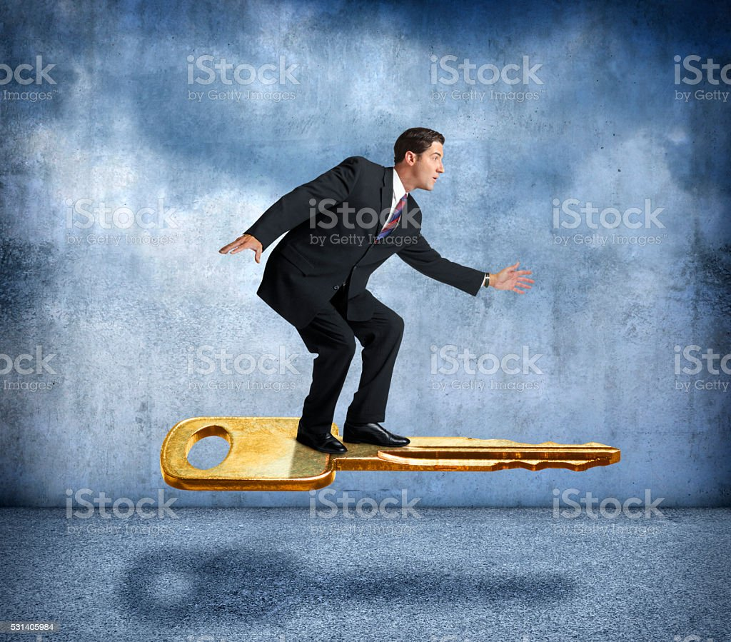 Businessman Riding On Golden Key To Success stock photo