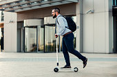 Businessman Riding Push Scooter.