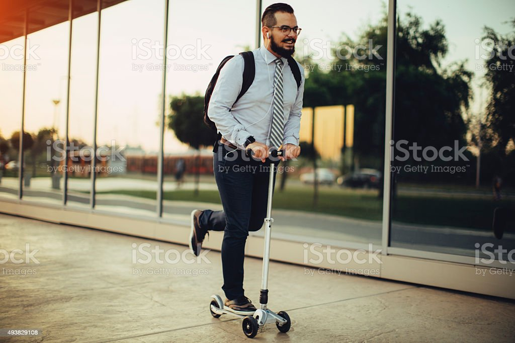 Businessman Riding Push Scooter. stock photo