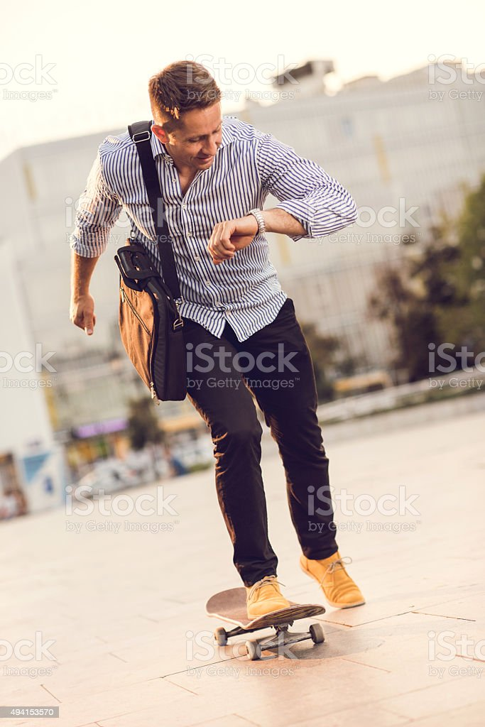 Businessman riding skateboard while checking the time on his watch. stock photo