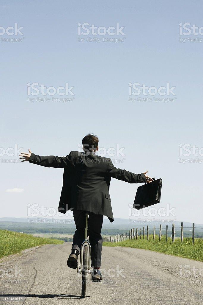 Businessman riding unicycle III stock photo