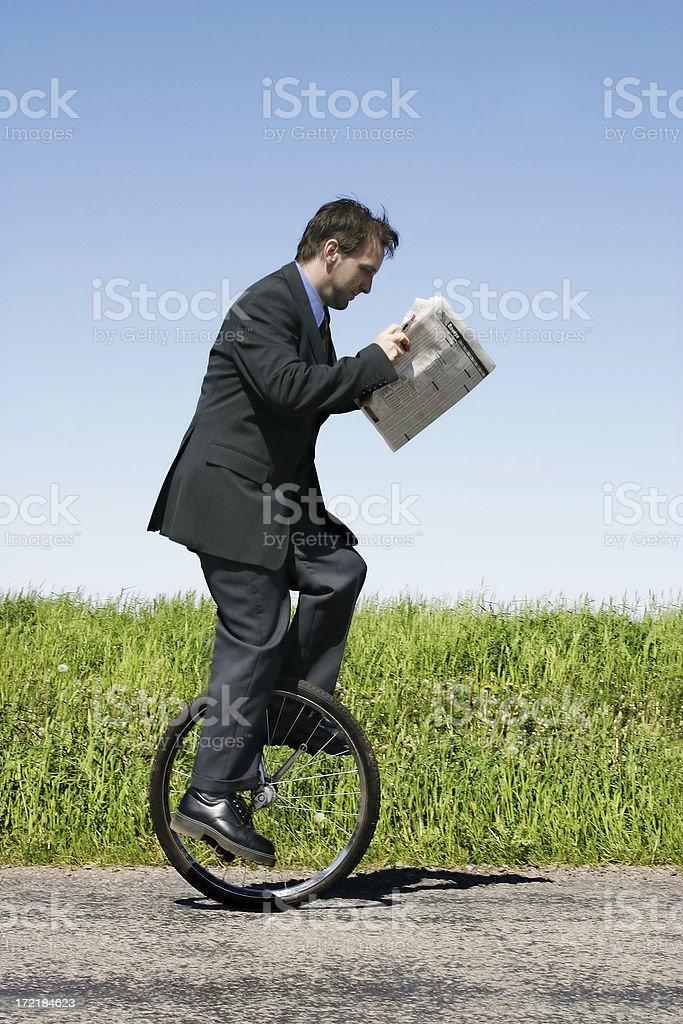 Businessman riding unicycle stock photo