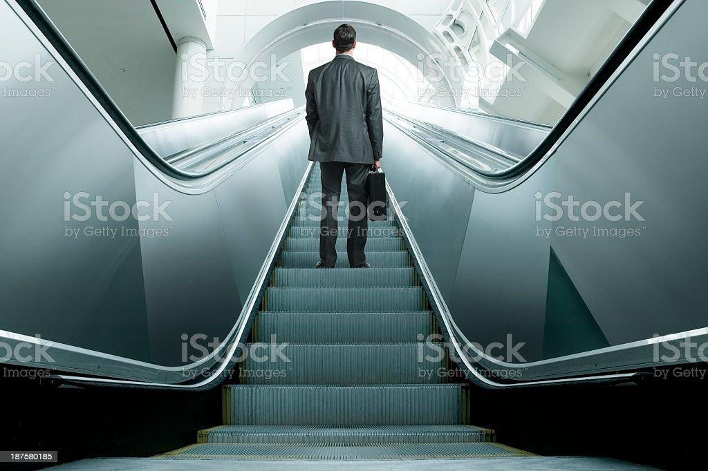 Businessman riding up an escalator stock photo