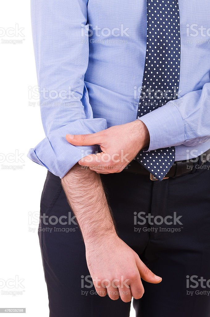 Businessman rolling up his shirt sleeves. stock photo