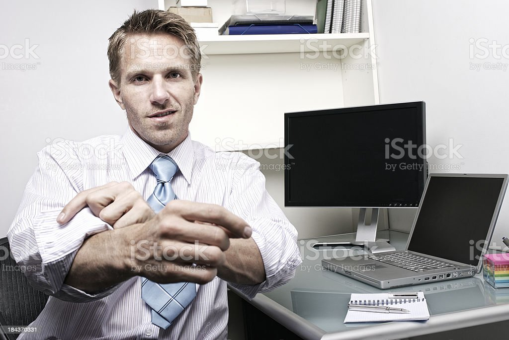 Businessman Rolls Up His Sleeves in Front of Computer stock photo