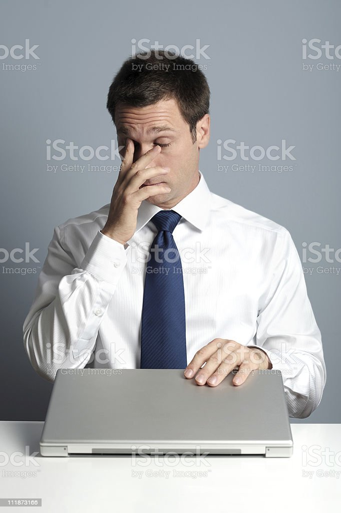 Businessman Rubbing Eyes and Closing Laptop Computer stock photo