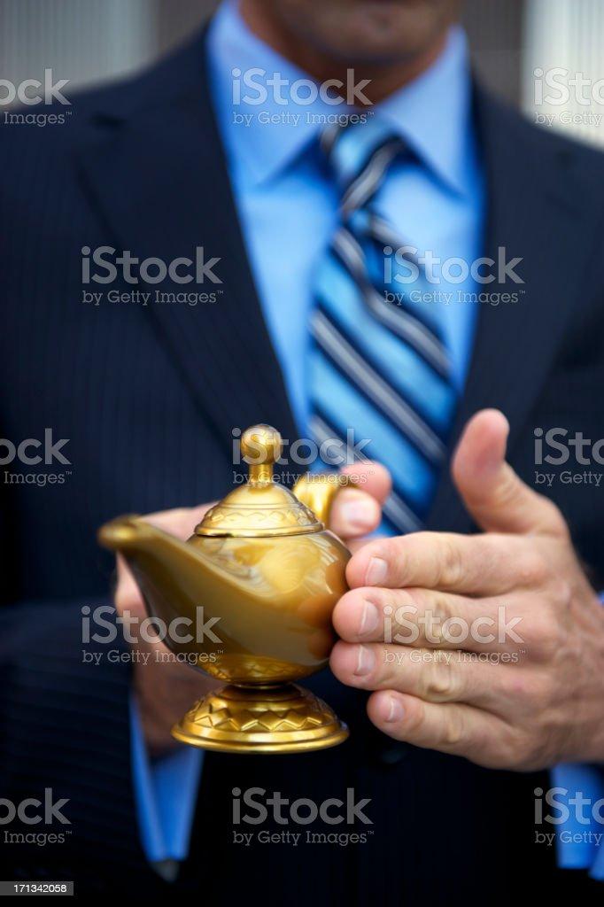 Businessman Rubbing Golden Magic Genie Lamp stock photo