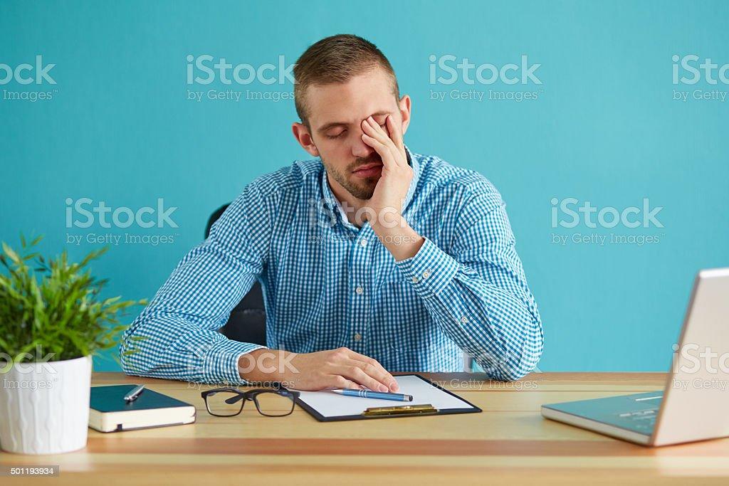 Businessman rubbing his eye stock photo
