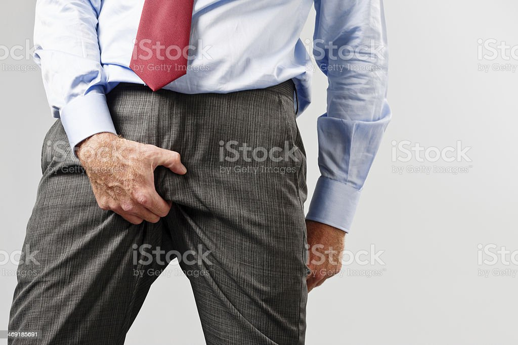 Businessman rudely grabs his crotch stock photo
