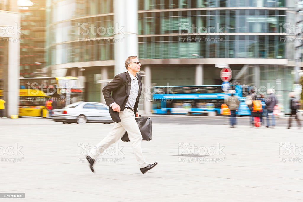 Businessman running in the city, panning image stock photo