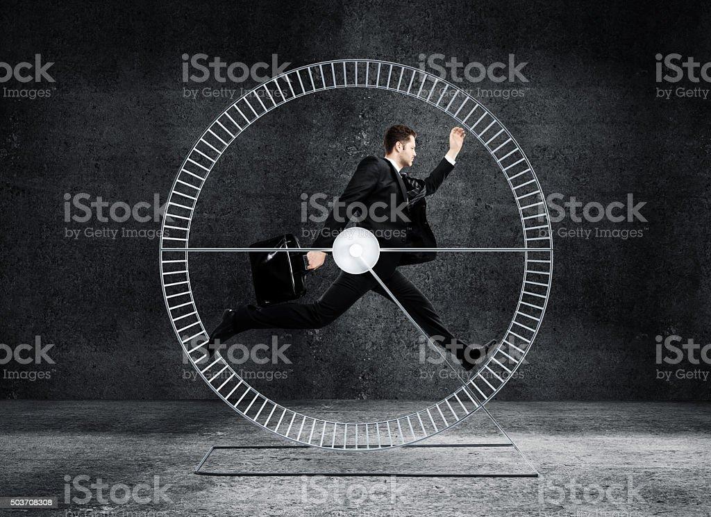 businessman running in wheel stock photo