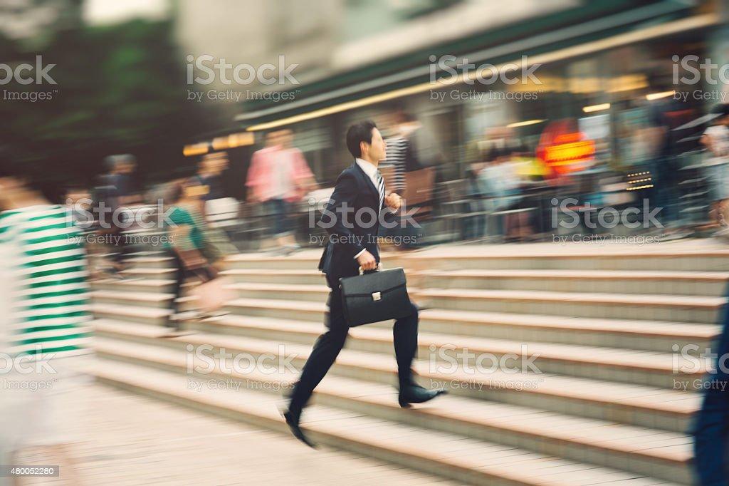Businessman running on the street stock photo